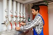 pic of boiler  - Young heating engineer in a boiler room for heating system - JPG