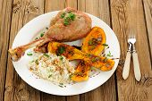 stock photo of butternut  - Roasted turkey leg with butternut squash pumpkin seeds and rice and two forks horizontal - JPG