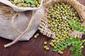 foto of chickpea  - Chickpea varieties in a burlap bag with green sprouts on a wooden background - JPG