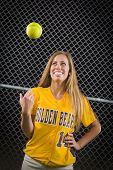 stock photo of softball  - Young Female Softball Player Portrait with Ball in the Air - JPG
