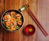 foto of rice noodles  - Vietnamese shrimp and rice noodles soup pho served on a wood table top - JPG