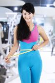 pic of measurements  - Attractive female fitness trainer use a measurement tape to measure her waistline at gym center - JPG