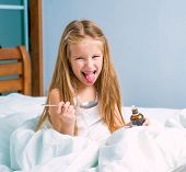 picture of cough syrup  - dissatisfied  little girl with influenza in bed - JPG