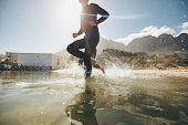 foto of triathlon  - Low angle view of young athlete running into water - JPG