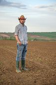 stock photo of farm land  - Portrait of Adult Male Farmer Standing on Fertile Agricultural Farm Land Soil Looking into Camera - JPG
