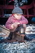 stock photo of tramp  - Vintage little child tramp with serious view sitting at a railroad track with a candlelight lantern in front of him and something to eat in his hand - JPG