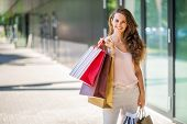 foto of shoulders  - A woman stands still her brown wavy hair swept to the side over one shoulder holding colourful shopping bags  - JPG