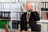 stock photo of bald head  - young businessman with bald head in the office is calling - JPG