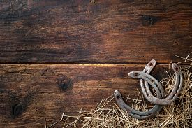 stock photo of horseshoe  - Two old rusty horseshoes with straw on vintage wooden board - JPG