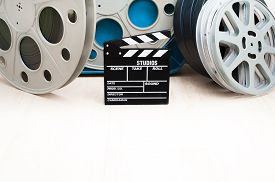 stock photo of mm  - Movie clapper board and 35 mm cinema reels with film and blue box - JPG