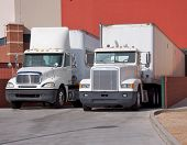 picture of loading dock  - Pair of trucks loading and unloading at large warehouse facility - JPG