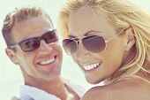 Instagram style photograph of happy and attractive man and woman couple wearing sunglasses and smili poster