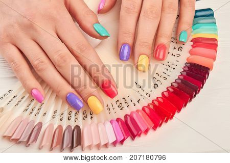 poster of Summer manicure and nail color samples. Young woman hands with multicolored manicure and collection of color nail polish samples. Nail beauty salon.