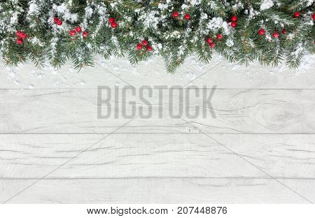poster of Christmas border out of natural Christmas tree fir twigs and red berries on a gray wooden background covered in snow with copy space.