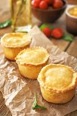 Delicious meat mini pies on parchment poster