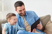 family, fatherhood, technology and people concept - happy father and little son with tablet pc compu poster
