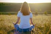 Woman Practices Yoga And Meditates In The Lotus Position On The Nature.  Girl Meditate At The Mounta poster