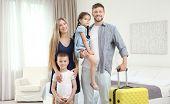 Family with luggage in hotel room poster