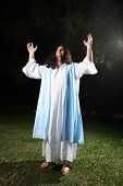 stock photo of glorify  - Biblical man wearing white robe and over cloak bathed in light praising and glorifying God - JPG
