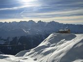 Chalet On Mountaintop In Swiss Alps In Winter