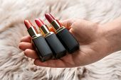 Woman Holding Different Lipsticks Over Furry Fabric, Closeup. Professional Makeup Products poster