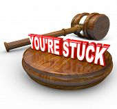 The words You're Stuck on a wooden block with a judge's gavel beside it illustrating that you are on