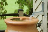 picture of downspouts  - Rain pouring into barrel to be used for gardening - JPG
