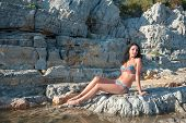 A Beautiful Brunette In A Bikini Is Sitting On A Stone. Sexy Brunette Girl In Bikini Posing On A Bea poster