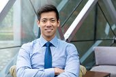 Portrait Of Young Smiling Handsome Asian Thai-chinese Businessman Sitting With Arm Crossed In Office poster