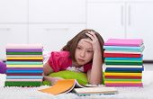Young girl tired learning laying among lots of books