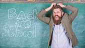 Hate School. Teacher Or Educator Stands Near Chalkboard With Inscription Back To School. Teacher Unh poster