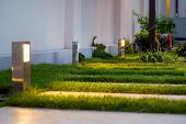 Garden Decorative Lantern Lighting Marble Walkway In The Evening Backyard With A Green Lawn, Closeup poster