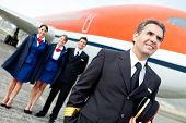 stock photo of cabin crew  - Captain pilot with cabin crew and an airplane at the background - JPG