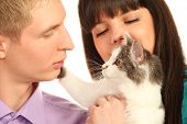 Young man and woman hold cat isolated on white background; Cat attacks man