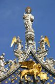 Vertical oriented image of sculptures on the rooftop of San Marco Basilica against blue sky in Venic