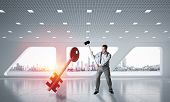 Determined Businessman In Modern Interior Breaking With Hammer Stone Key Figure poster