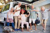 Portrait Of Excited Senior Friends Loading Luggage Into Trunk Of Car About To Leave For Vacation poster