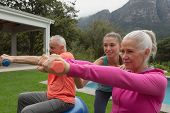 Side view of Caucasian female trainer assisting active senior Caucasian couple to exercise with dumb poster