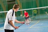 stock photo of badminton player  - Man get ready to start next rally focus on man in front - JPG