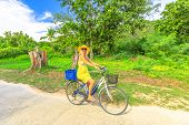 Elegant Happy Woman In Yellow Dress Cycling Around La Digue Island In Seychelles. Happy Lifestyle In poster