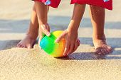 Baby Feet Walking On Sand Beach Grabbing Rugby Ball - Playful Toddler Wearing Inflatable Armbands Ha poster