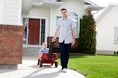 Father pulling son in a wagon in front of house on sidewalk