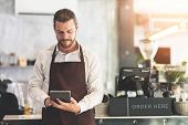Male Barista Holding And Looking At Digital Tablet At The Coffee Shop Or Restaurant Cafe. Startup Of poster