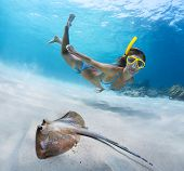 Underwater shoot of a young lady snorkeling and doing skin diving over sandy sea bottom with blue sp
