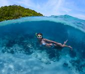 Underwater shoot of a young lady doing skin diving in tropical sea with green island on the backgrou