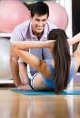 Athletic woman does situps with coach in training gym