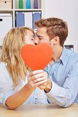 Young couple kissing hiding behind a big red heart in the living room