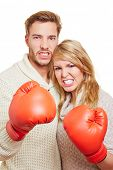 Aggressive couple fighting with two red boxing gloves