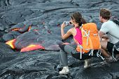 Hawaii lava tourist. Tourists taking photo of flowing lava from Kilauea volcano around Hawaii volcan