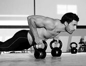 Sportschool man push-up kracht pushup met Kettlebell oefening in een training